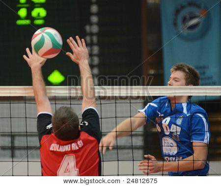 KAPOSVAR, HUNGARY - OCTOBER 29: Roland Gerggye (R) in action at a Hungarian National Championship volleyball game Kaposvar (blue) vs. Szolnok (red), October 29, 2011 in Kaposvar, Hungary.