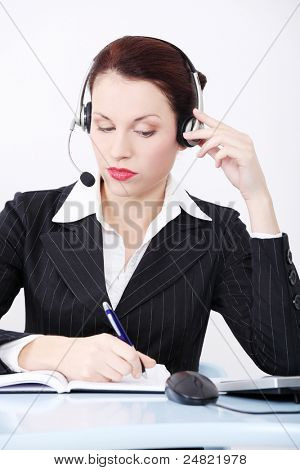 Pretty caucasian smiling businesswoman in headset sitting in the office and writing something in calendar.