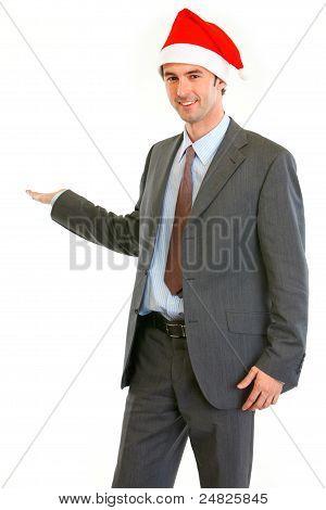 Smiling Modern Businessman In Santa Hat Showing Something