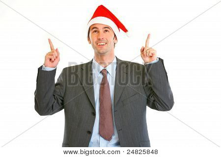 Smiling Modern Businessman In Santa Hat Pointing Up
