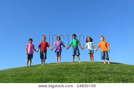 Group of kids standing on grass hill with blue sky