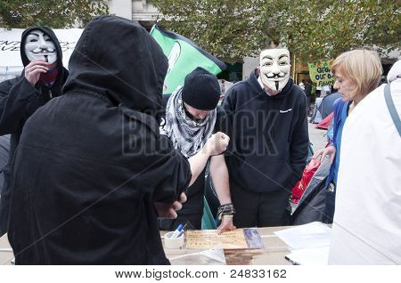 LONDON, UK - OCTOBER 31: Protesters wearing masks are answering questions of public and giving away banners at anti capitalist protests near London Stock Exchange  on October 31, 2011 in London.