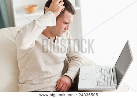 Confused young man using a notebook in his living room