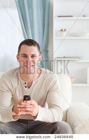 Portrait of a man sending text messages while sitting on a sofa in his living room