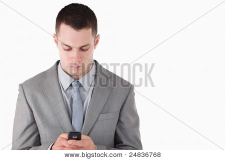 Businessman dialing on his cellphone against a white background