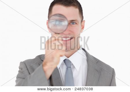 Young businessman looking through a magnifying glass against a white background