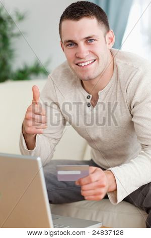 Portrait of a man purchasing online with the thumb up in his living room