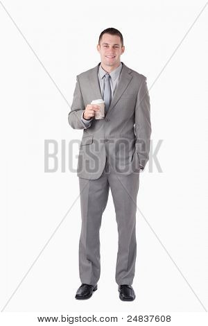 Portrait of a businessman holding a cup of tea against a white background
