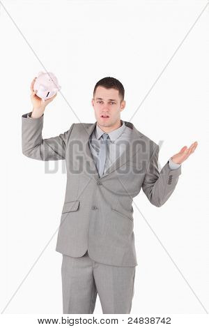 Portrait of a broke businessman shaking an empty piggy bank against a white background