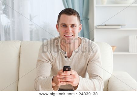 Man sending text messages while sitting on a sofa in his living room