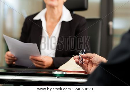 Mature female lawyer or notary with client in her office for counseling