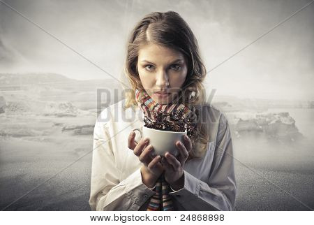 Young woman in winter clothes holding a cup of hot drink