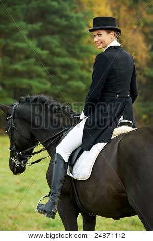 horsewoman jockey in uniform riding horse outdoors