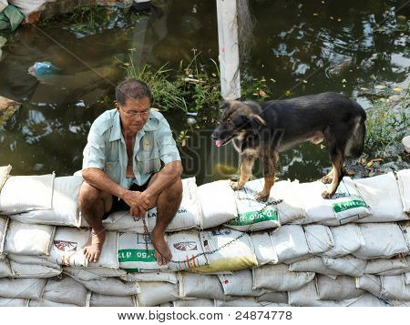 PHATHUMTRANI, THAILAND- OCTOBER 21: Flood victim with his dog sits on sand bags, during the worst flooding disaster   on October 21, 2011 Rongsit Road, Phathumtrani, Thailand.