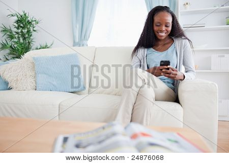 Smiling woman writing text message while sitting on sofa