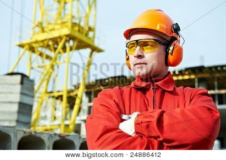 builder worker in uniform and safety protective equipment at construction site