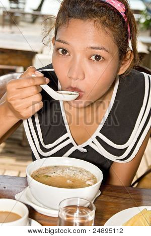 girl tastes the boiled rice