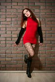 stock photo of hooker  - girl dressed like hooker posing near brick wall - JPG