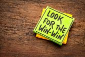 look for win-win concept  - handwriting on a sticky note against grunge wood board poster