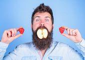 Fruit Filling. Man Handsome Hipster Long Beard Eat Apple Hold Strawberry. Hipster Surprised Enjoy Fr poster