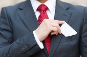 Closeup Of Businessman Hand Holding A Business Card Over Suit Pocket Isolated On White. Businessman  poster