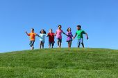stock photo of ethnic group  - Kids running on grass hill with blue sky - JPG