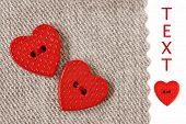 Extreme closeup of tiny heart shaped buttons sewn on natural cotton fabric with white background and