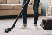 Close Up. Woman In Jeans Cleans Carpet With Vacuum Cleaner. Professional Janitor Vacuuming White Car poster