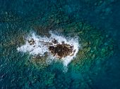 Aerial above waves crashing against a rocky outcrop in shallow tropical sea water poster