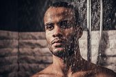 Young Afro-american Man Taking Shower In Bathroom At Morning. Standing Man With Bare Torso In Bathro poster