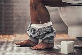 Close Up. Handsome Young Afro American Man Sitting On Toilet In Bathroom At Morning. Personal Mornin poster