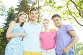 Four affectionate friends in casualwear standing in park on sunny day poster