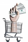 Manikin hand in a miniature shopping cart, holding money