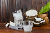 Coconut Milk Glass With Coconut Half And Coconut Pieces And Leaf  On Wooden Table .close Up. poster