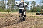 An Image Of A Dirt Bike Racer On A Muddy Dirt Race Track. poster
