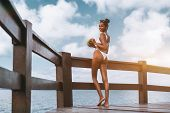 Cheerful Sexy African-american Girl In A White Swimsuit Half-turned To The Camera, Is Standing On Th poster