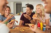 Cheerful friends enjoying pizza together at home. Happy smiling men and young women sharing pizza fo poster