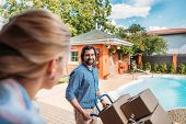 Smiling Man With Handle Tray With Cardboard Boxes Looking At Wife On Porch Of New House, Moving Home poster