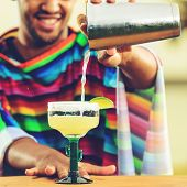 Close-up Of Handsome, Smiling Mexican Bartender Standing On The Bar Counter On The Beach And Adding  poster