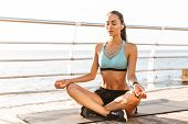 Image of sporty fitness woman 20s in sportswear sitting on exercise mat in yoga pose and meditating  poster