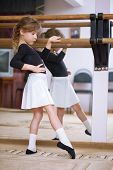 Girl at ballet barre. Ballet pas. Right profile. Reflection in mirror.