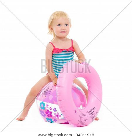Baby Girl In Swimsuit With Inflatable Ring Sitting On Ball