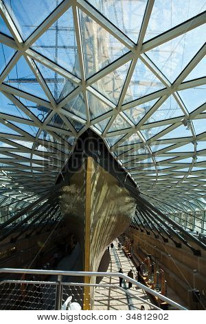 LONDON, ENGLAND - 13 JULY : Visitors stroll beneath the Cutty Sark.