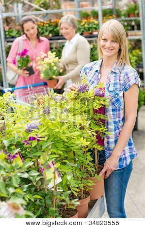 Smiling woman at garden centre shopping for house plants