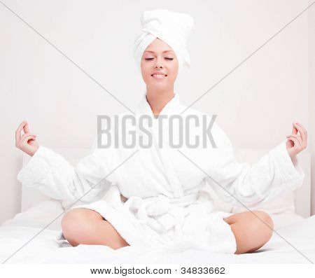 beautiful young woman wearing a towel and a white bathrobe meditating in  the bed at home