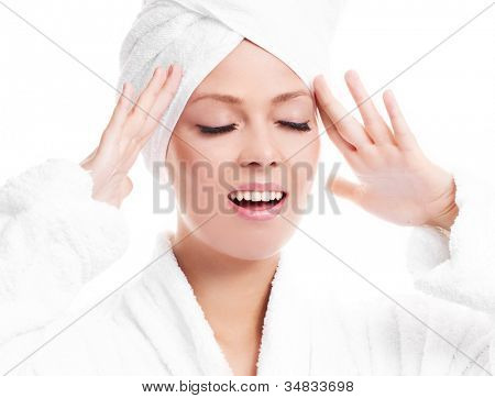 beautiful young woman wearing a towel and a white bathrobe  massaging her face, isolated against white background