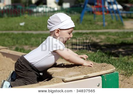 Happy Boy Playing In Sandbox