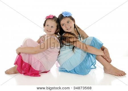 Two young girl friends, sitting back to back in look-alike sundresses, except one is pink and the other is blue.  On a white background.