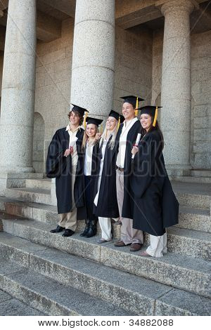 Graduates posing while smiling in front of the university