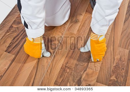 Worker Analyzing Wooden Floor For Cracks